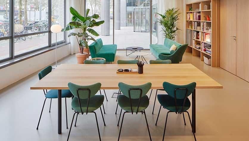sillas verdes en un espacio de oficinas precioso para una entrada de blog sobre darle vida a tu mesa