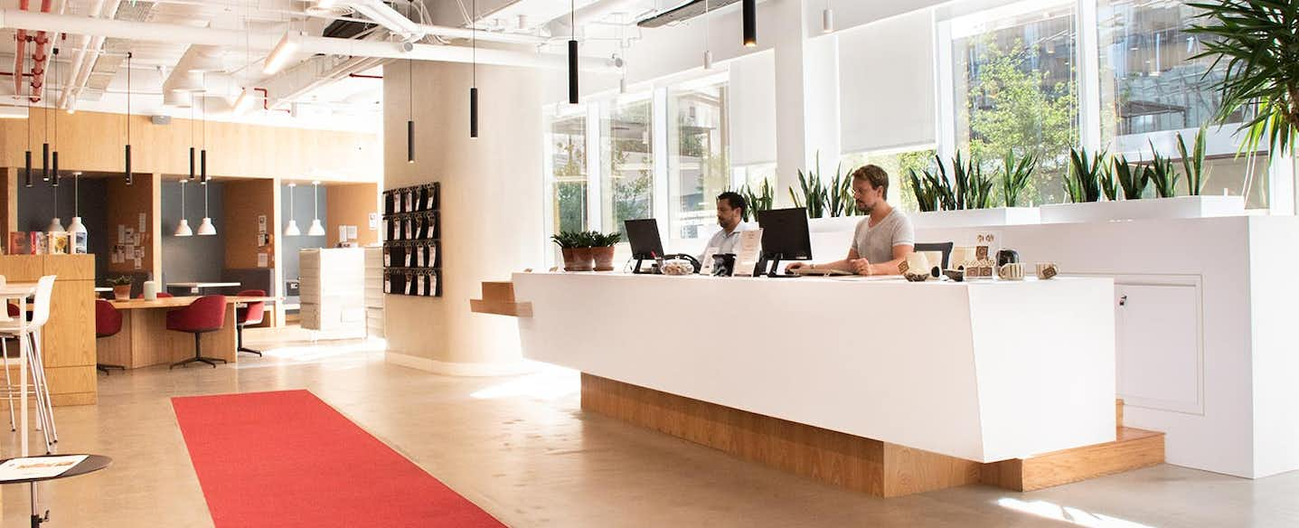 front desk with people behind computer and a red walker on the ground