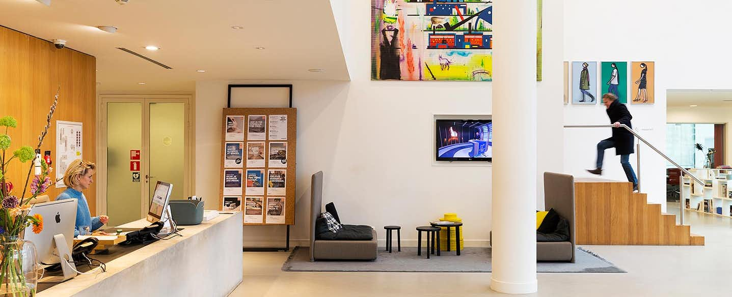 Front desk with woman sitting behind it on computer and a man walking up the stairs with art on the walls