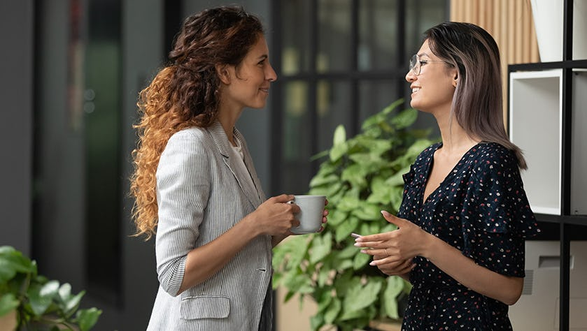 Multiethnic female colleagues chat during coffee break