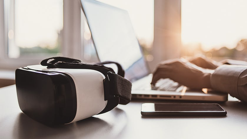 Business man using laptop computer with VR headset. Focus on vir