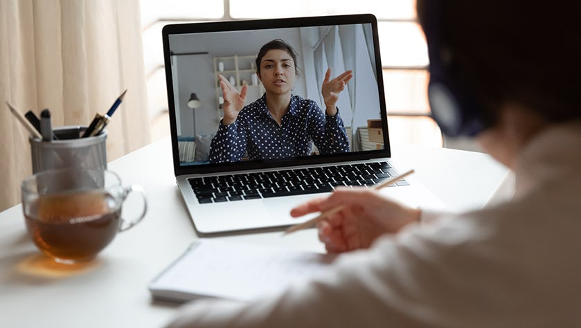 Millennial girl employee talk on video call with female colleague
